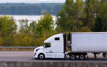 Modern and comfortable, popular model heavy trucks with aerodynamic body and refrigerated trailer on the highway with a concrete separation barrier and the markings on the background of the river and green trees in the Columbia Gorge.
